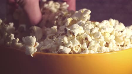 cinematography : A man takes fresh hot popcorn from a bowl. A male hand picks popcorn from a bucket.