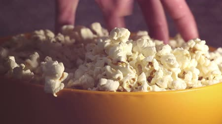 жадный : A man takes fresh hot popcorn from a bowl. A male hand picks popcorn from a bucket. A man grabs popcorn from a bucket while watching TV.