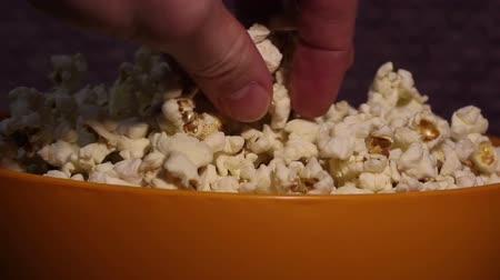 グラブ : A man takes fresh hot popcorn from a bowl. A male hand picks popcorn from a bucket. A man grabs popcorn from a bucket while watching TV.
