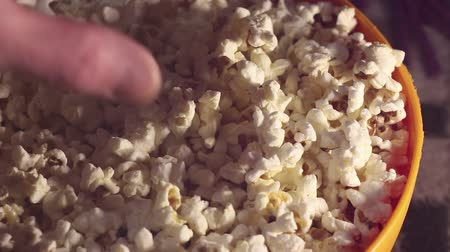 жадный : A man takes fresh hot popcorn from a bowl. A male hand picks popcorn from a bucket.