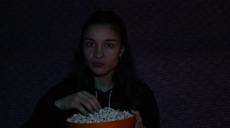 comics pop : Young attractive girl is eating popcorn and she is watching TV enthusiastically.