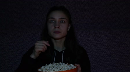 comics pop : A young girl watching TV and eats popcorn.Young beautiful girl sits on a sofa at home watching her favorite movie on TV. Stock Footage