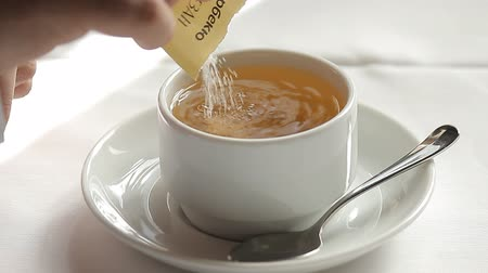 mroczne : Adding sugar to cup of tea and stirring
