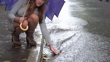 ulewa : Young beautiful woman sat down by the roadside with an open umbrella and wets his hands in the stream under heavy rain Wideo