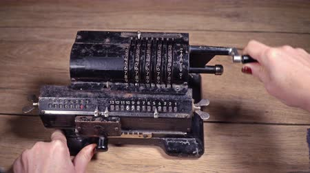 aritmética : Female hand turning the handle of the old, rusty adding machine, standing on a wooden table Stock Footage