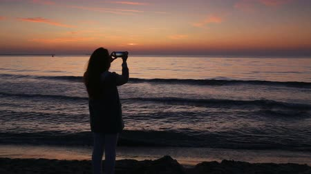 Румыния : Young woman taking photos with her smartphone, on the beach, at sunrise