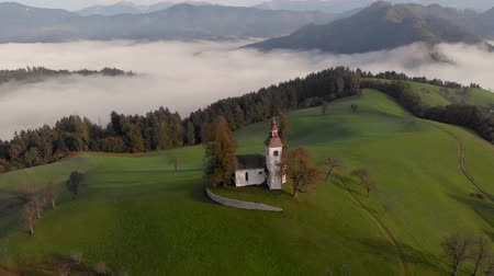 Autumn aerial view of a beautiful church on the top of a hill, in Slovenia Стоковые видеозаписи