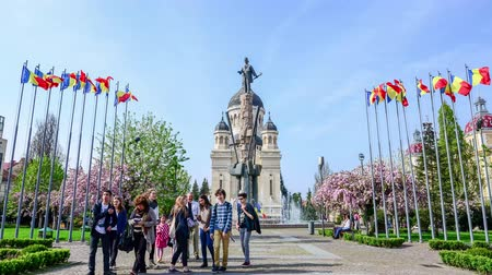heroes square : Cluj-Napoca, Romania - 10 April: Orthodox Cathedral, Avram Iancu Statue and Square with tourists in front of the fountain posing and looking at the monument of the national hero Stock Footage