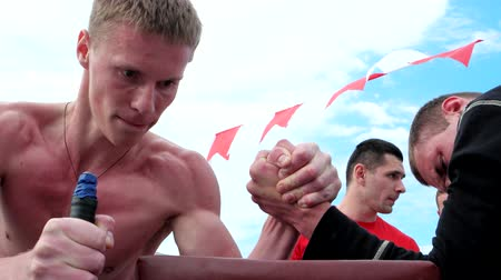 might : Kherson, Ukraine - 01 june 2016: Arm wrestling, competition power of men on the street in Kherson 01 june 2016. young men athletic, competing in arm wrestling, sports competitions.