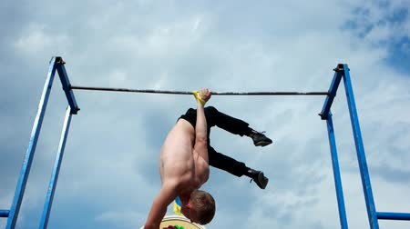 lift ups : Kherson, Ukraine - 01 june 2016: Strong muscular guy doing exercises athletics on a transverse crossbar in Kherson 01 june 2016. Male gymnast participated in competition athletics, outdoor sport