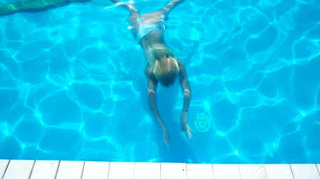 uszoda : girl floats under water in the pool comes up, girl with a beautiful figure floating under the blue water in a white bathing suit, emerge of the swimming pool wet blonde long hair fall on the shoulders
