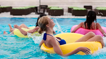 tüp : girl swimming in a pool on inflatable circles, Floating Ring, Sexy happy girl float sends an air kiss, happy girlfriend squirting blue pool water. young woman splatter in swimming pool, summer resort Stok Video