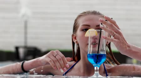 banhos de sol : A girl swims to the blue alcoholic cocktail. young girl floating in the pool, close to the side of the road the edge of the pool with blue water takes an alcoholic drink takes a sip of alcohol through