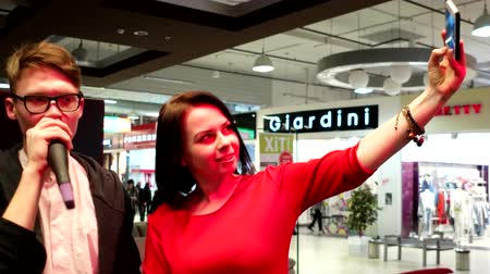vocação : Kherson, Ukraine - 28 March 2016: selfie with the lead manager of the festival at the mall in Kherson 28 March 2016. girl making photo mobile phone posing near a guy who speaks into the microphone