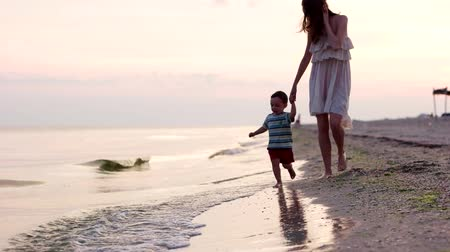 лечит : Mother and son walking the beach. child his mother running around barefoot in the sand on the beach. family on holiday happiness fun in the marine reserve heals and rests mother and son happy together