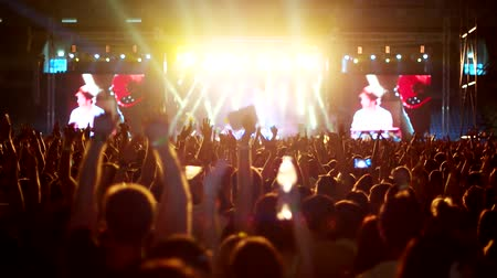 koncert : raised hands at a rock concert simultaneously clapping, crowd of spectators on the background brightness of the scene, bright colored lights shine on the large number of people, outdoor concert