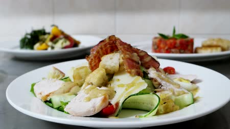 césar : Caesar salad with chicken and slices of bacon, several ready-meals are on a professional restaurant kitchen ready for the table, beautiful food for customers