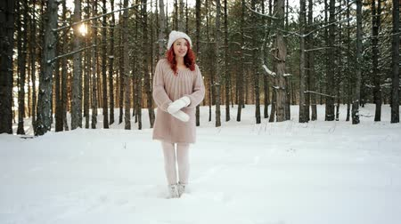 congelado : frozen girl beautiful model in the winter forest, jumping, dancing, girl trying to warm active movements, winter nature, frosty weather, a young woman with red hair in a warm knitted sweater