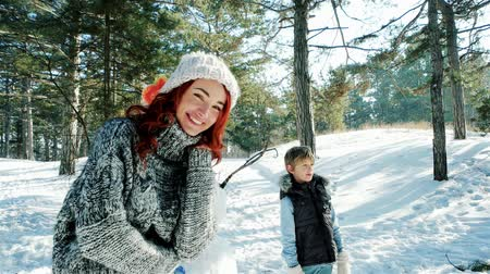 mittens : happy mother and son spend together a winter vacation, family sculpts snowman, snow sculptures decorate, parents and children walking outdoors in winter forest Stock Footage