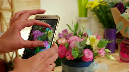 képek : flower arrangements, cell phone takes pictures of the finished bouquet of fresh cut flowers, pictures of flowers, florist photographed on a smartphone in the floral boutique, Stock mozgókép