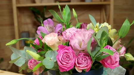 arranjo : beautiful fresh flowers is a good gift for a holiday, Golan roses on the counter for customers, flower shop, boutique, ready to flower bouquet