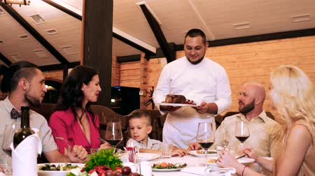 обедающий : chef comes out to the customers of the restaurant, serves grilled meat, family in restaurant, great food and alcoholic drinks on table, group of friends and relatives sit around a table