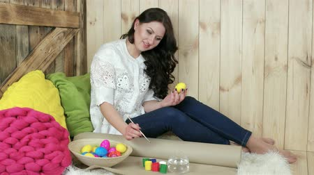koszyk wielkanocny : holiday crafting, smiling girl decorates easter eggs, wicker plate full of colorful eggs, wooden background, easter preparation, eggs painting, handmade bright things for celebration