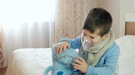 alerji : Nebulizer for inhalation, sick child breathes through nebulizer, baby does inhalation, boy with an oxygen mask on his face, treatment at home, medical procedure
