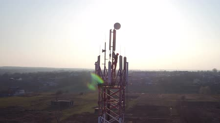 вещание : worker on great heights of cellphone tower, maintenance personnel servicing cellural antenna, drone view of telecommunication repeater antenna system, aerial round view of cellphone tower near village
