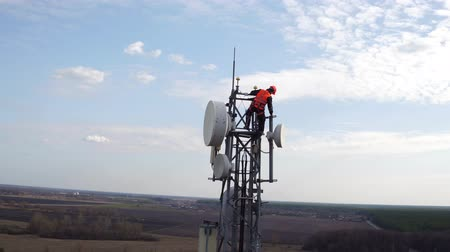 вещание : worker servicing cellular antenna in front of sunlight, drone view of telecommunication antenna system, technician working on top of cellular antenna, industry of telecommunication engineering