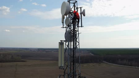 башни : man working on radio telecommunication tower, radio master works at great heights of tv tower, industry of telecommunication engineering, drone flying around outdoor repeater base station tower