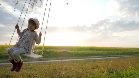 подача : Cute little kid girl portrait sit on swing in nature sunset light background, Happy little child have fun sway spin on swing, kid swaying nature in forest park, slow motion