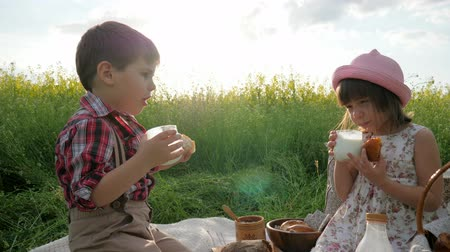 восхищенный : Kids eat milk with bun, Enjoy meal, Slow motion in Backlight, picnic on background flowers, Friends drink milk, joy, Bread in babys hands, Family at sunset, Picnic for children on nature