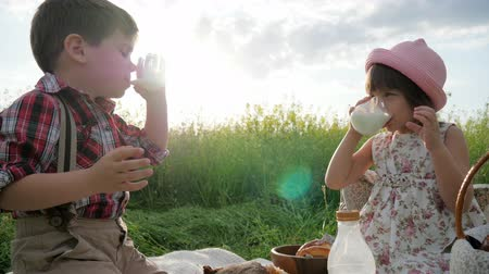 important : Friends on picnic on background with flowers, glass of milk in backlight, Children clink glasses, Family enjoy milk, Children grimace, hamming of face, Slow motion in Backlight