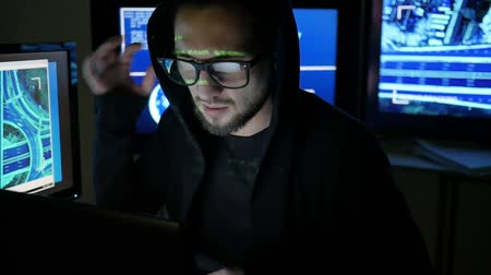 süzülme : Male hacker working on computer while green code characters reflect on face in dark office room, Internet espionage, Criminal hacker cracking system, Computer Terrorism, Hacker portrait