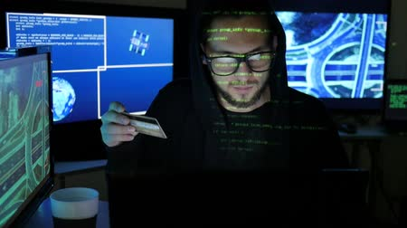 süzülme : Cyber criminal hacker Holds in hands stolen bank card, steal finances through the Internet, male Hacker cracking Banking system, using laptop, computers, Hacker portrait, Computer Terrorism Stok Video