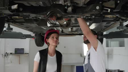 motorháztető : Professional maintenance people concept, cars service worker Advised client, helps feminine customer on station, male master Checks Technical condition auto, female vehicle break