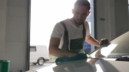 tření : mechanic Prepares machine for client, Car wash, backlight, portrait of man rubbing automobile body, slow motion, worker auto repair, staff service station, male master