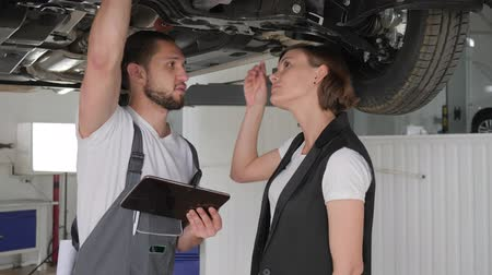 csavarkulcs : female consumer in car service, feminine vehicle broken, guy pro advises client, woman and master near machine, visitor in auto repair, service book in hand auto mechanic, mechanic helps customer, Stock mozgókép