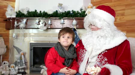 fire arms : little kid telling santa his christmas wishes, room with fireplace, boy visiting santa claus winter residence, sweets for good and obedient children, holiday atmosphere, child sit on saint nicolas lap Stock Footage