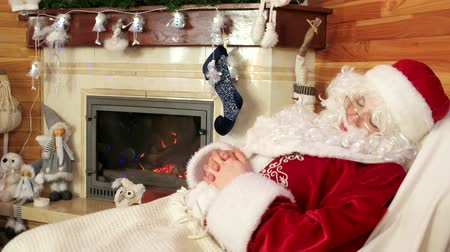 Навидад : sleeping sana claus, old tired santa snoozing after hard work, leisure time, room with fireplace and decorated christmas tree, saint nicolas resting at his residence, gaining strength before holidays Стоковые видеозаписи