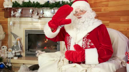 konuksever : santa greeting visitors, hospitable santa claus, saint nicolas welcomes kids visit him at his winter residence, fireplace and decorated christmas tree, holiday atmosphere, saying hello and waving hand Stok Video