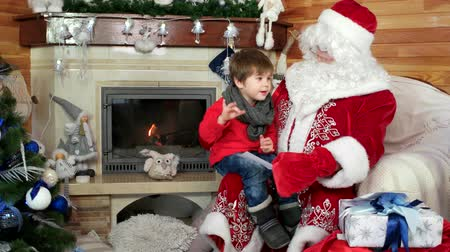 Навидад : boy sitting on santas lap, child giving saint nicolas his cristmas wishlist in envelope, holiday atmosphere, room with fireplace and decorated christmas tree, kid visiting santa claus residence