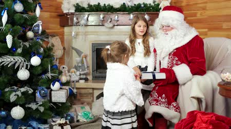 záradék : little girls visit santa at his residence, happy sister sitting on santa claus lap, christmas gifts for good and obedient children, holiday atmosphere, room with fireplace and decorated christmas tree Stock mozgókép
