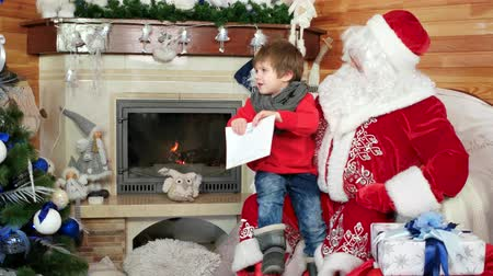 Навидад : little boy sitting on santas lap, kid visiting saint nicolas winter residence with hristmas letter, room with fireplace and decorated christmas tree, holiday atmosphere, gifts for good and children