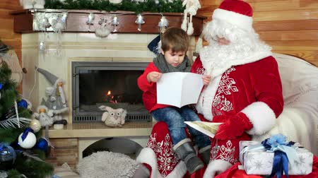 Навидад : little boy opening his christmas letter, child sit on santas lap, kid visiting saint nicolas residence with wishlist in envelope, holiday atmosphere, room with fireplace and decorated christmas tree