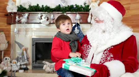 fire arms : little boy telling santa his christmas wishes, child sitting on saint nicolas lap, big gifts for obedient children, holiday atmosphere, kid visiting santa claus winter residence, room with fireplace