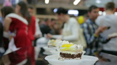 šlehačka : Close-up cream cake in disposable tableware on table, piece of pie on plate in hands, Blurred silhouettes, cut pieces, serves guests supermarket, treat for visitors to shopping center, Celebrate, Dostupné videozáznamy