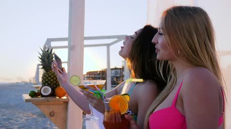 luksus : girlfriends photographed on mobile phone, drinking cocktail on sea shore in sunset, exotic fruits on beach, happy holidays in warm countries, rich vacation girls on tropical islands, Wideo