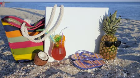terlik : exotic fruits on coast near ocean, still life tropical fruits, set for beach holidays, pineapple in sunglasses, coconut colored cocktail on hot sand, flip-flops with fruits and bag on shore sea,